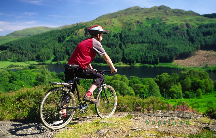 Glen Trool near Bruces Stone cyclist looking across Loch Trool to Mulldonoch hill in the Galloway Forest Park Dumfries and Galloway Scotland UK