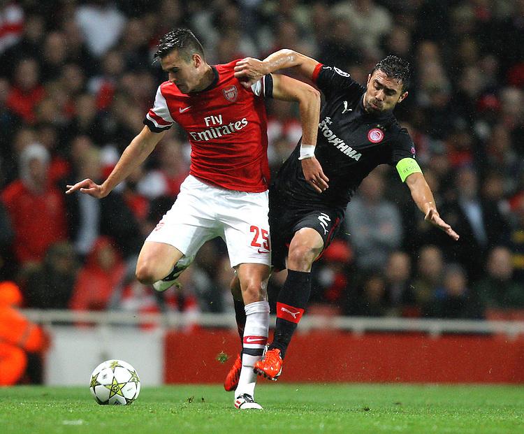 Arsenal's Carl Jenkinson battles with Olympiakos' Giannis Maniatis ..Football - UEFA Champions League Group B - Arsenal v Olympiakos FC - Wednesday 3rd October 2012 - Emirates Stadium - London..