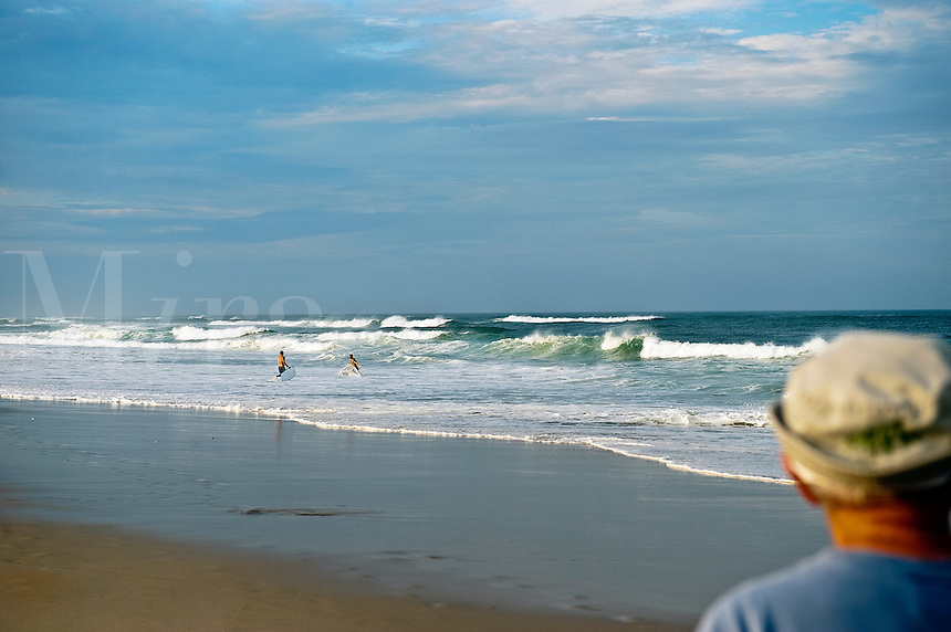 Mature man watches surfers, Cape Cod National seashore, Cape Cod, MA