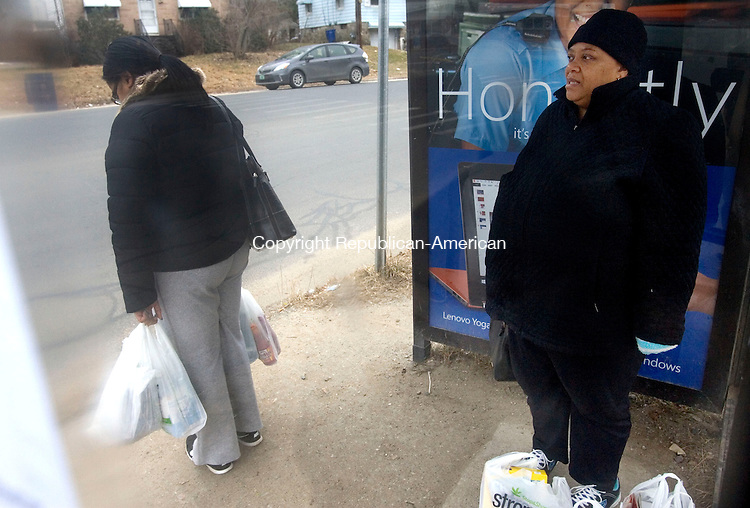 WATERBURY CT. 21 January 2014-012014SV03-Tia Iverson, right, tries to stay warm while waiting for the bus after grocery shopping on North Main Street in Waterbury Tuesday.<br /> Steven Valenti Republican-American