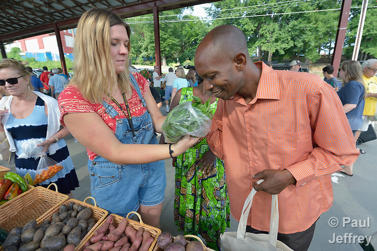 Monique Lohmeyer, a case manager for Church World Service, helps Casmil Ngundakumana, a refugee from Rwanda, to experience basil and other products available in the Durham Farmers' Market in Durham, North Carolina. The market's Double Bucks program allows consumers with EBT cards to double their purchasing power.<br /> <br /> Church World Service resettles refugees in North Carolina and throughout the United States.<br /> <br /> Photo by Paul Jeffrey for Church World Service.
