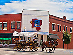 A covered wagon, pulled by mules, crosses the Independence, Missouri Square in front of the Ophelias Restaurant.