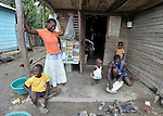 A family gathers on the porch of their home in Batey Bombita, a community in the southwest of the Dominican Republic whose population is composed of Haitian immigrants and their descendents. The man is grating cassava for a meal.