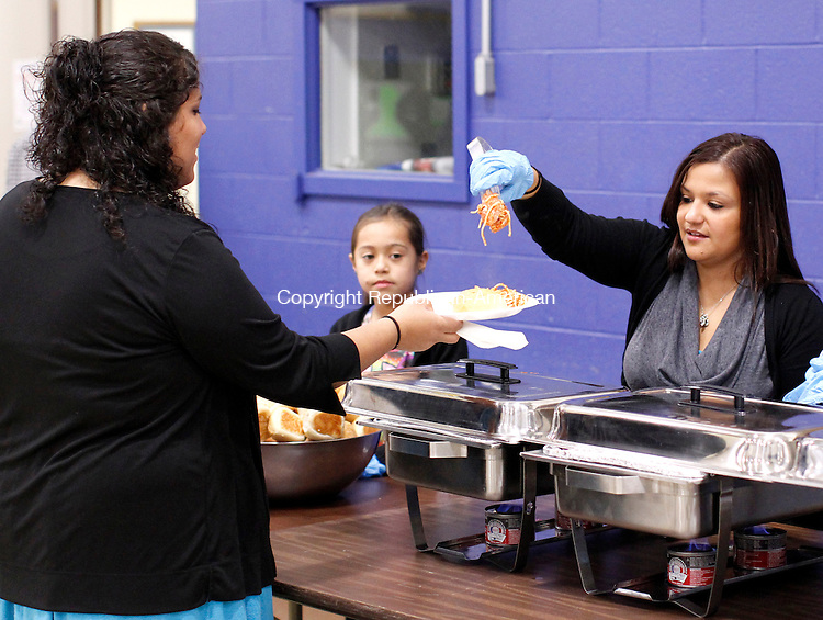 WATERBURY, CT-12 December 2011-121211CM04-  Elsie Alvarado (right) staff member of Waterbury's High Road School, serves dinner to Samantha Algarin, a family friend of Cody Maldonado, who the dinner benefited Monday night at the Waterbury Police Activity League.  Maldonado, a 17 year old student at High Road, was diagnosed with Ewing's Sarcoma, a form of cancer.  The dinner and raffle was to support Maldonado and his family. Staff from the school helped organize and volunteer at the event.     Christopher Massa Republican-American