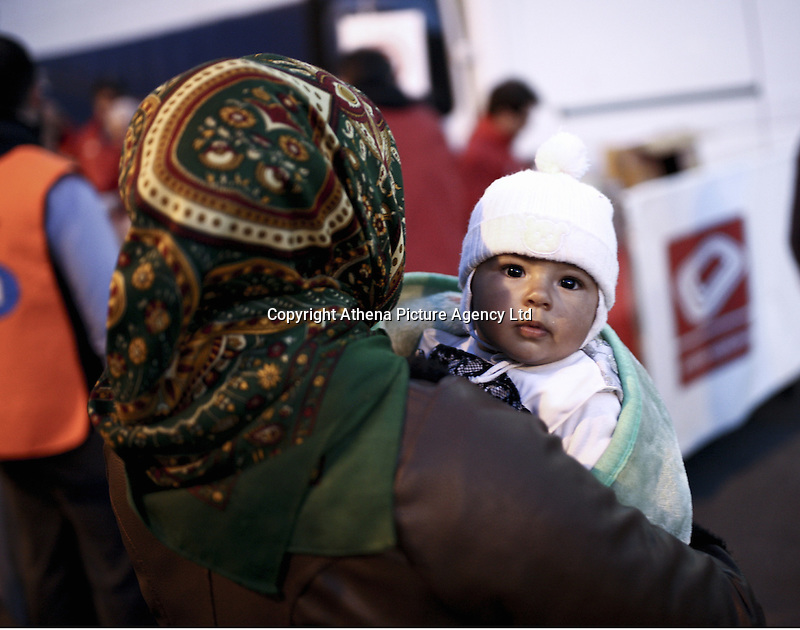 Pictured: A baby is held by his mother Monday 07 March 2016<br /> Re: Migrants have been gathering at the port of Piraeus, near Athens, Greece.