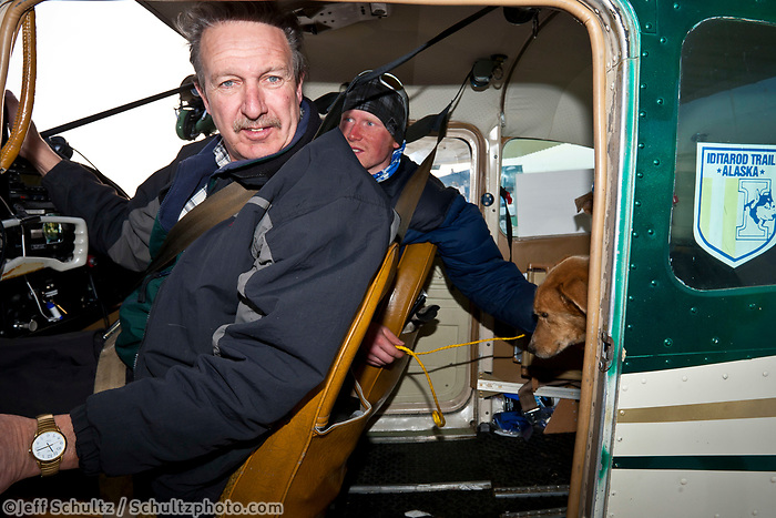 Pilot Danny Davidson and scratched musher John Stewart unload his dogs after arriving in Nome during the 2010 Iditarod