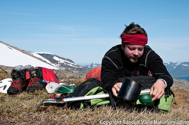 Mann med morgenkaffe under åpen himmel på Seiland. ---- Man in sleeping bag making coffe.