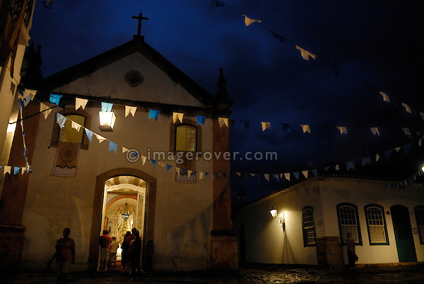 """Paraty, Espirito Santo, Brazil: The church parade at the Festa de Sao Benedito has reached the small church """"Igreja de Nossa Senhora do Rosário e São Benedito"""" in the historic centre of Paraty. --- Info: The Nossa Senhora dos Rosarios and Sao Benedito (Church of Our Lady of the Rosary and Saint Benedict) was built and used by Paraty's African slaves. It dates back to the year 1725. The church has a much simpler, more rustic style than the other three churches in Paraty. The beautiful colonial town of Paraty has been a UNESCO World Heritage Site since 1958.  --- No signed releases available."""