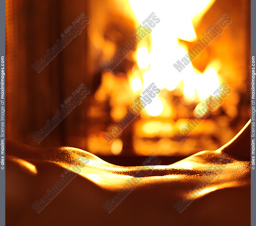 Nude shiny woman body, sensual closeup of stomach, lying in front of a burning fireplace