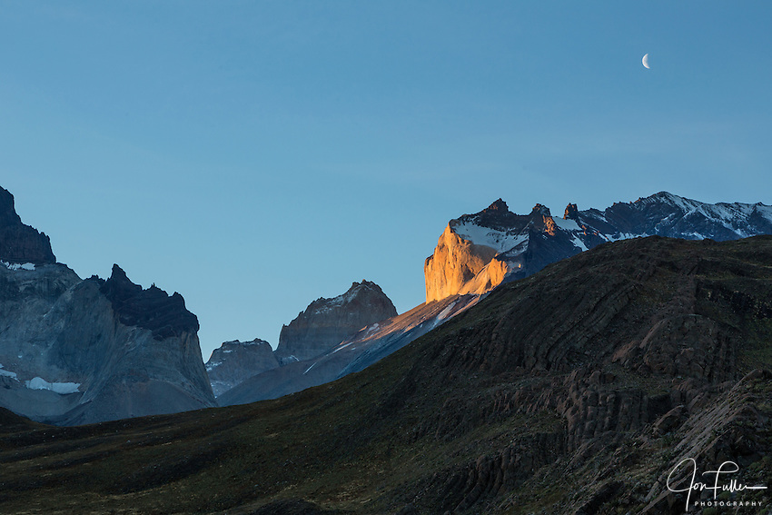 Sunset light on the yellow granite face of Monte Almirante Nieto.  Just to the left is the top of Torre Sur, or the South Tower, of the Torres del Paine.  The crescent moon is in the sky above.  Snow caps the black sandstone overlaying the granite layer.  Torres del Paine National Park in Patagonia, Chile.  A UNESCO World Biosphere Reserve.