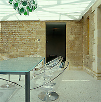 The modern conservatory extension combines several different materials - the old stone walls of the house, the resin and pebble floor and the clear surfaces of the furniture