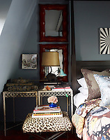 A pair of wrought iron garden tables displays a model tank beside the four-poster bed in the guest bedroom