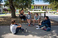 Students talk on a bench in the Academic Quad at the start of Reading Days, May 1, 2019.<br /> (Photo by Marc Campos, Occidental College Photographer)