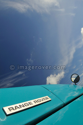 Bonnet and badge on freschly restored very early classic 1970 Range Rover against blue sky. UK, England, Dunsfold 2005. --- No releases available. Automotive trademarks are the property of the trademark holder, authorization may be needed for some uses. --- This RR in Tuscan Blue is registered as NXC245H (VIN 35500040A) which means it is one of the first models used as a press release vehicle. In May 1970, a batch of 20 production standard Range Rovers were built for the press launch in May/June 1970 at the Meudon Hotel near Falmouth, Cornwall. These Range Rovers were assigned Solihull registrations NXC 231H to NXC 250H consecutively with chassis numbers 35500025A to 35500045A. The Range Rover was available as a three door estate only with a 3.5 ltr. V8 pertol engine, four speed manual gearbox and permanent four wheel drive.