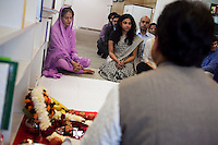 Staff and guests sit on the floor barefooted in respect of the puja (prayer and blessing) at the opening ceremony of the new Bill & Melinda Gates Foundation office in New Delhi, India on 17th December 2010. Photo by Suzanne Lee for Gates Foundation