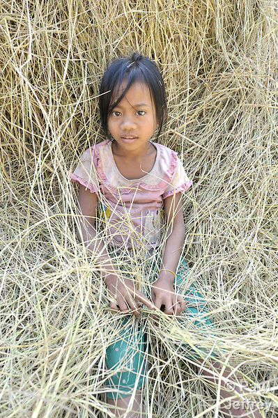 Nine-year old Att Nimol rests among rice stalks in the Cambodian village of Solang Kandal.