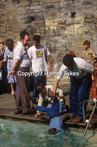 St Winefrides Shrine, Wales. Gypsy father lowers child into spring water healing pool. Holywell Flintshire Wales. 1990s.<br /> <br /> St Winifred or Saint Winefride was a 7th-century Welsh Christian woman, around whom many historical legends have formed. A healing spring at the traditional site of her death is now a shrine and pilgrimage site called St Winefrifdes Well, known as the Lourdes of Wales.