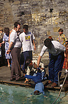 St Winefrides Shrine, Wales. Gypsy father lowers child into spring water healing pool. Holywell Flintshire Wales. 1990s.<br />