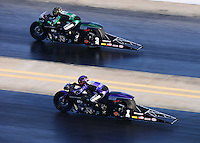 Sept. 14, 2012; Concord, NC, USA: NHRA pro stock motorcycle rider Andrew Hines (far lane) races alongside teammate Eddie Krawiec during qualifying for the O'Reilly Auto Parts Nationals at zMax Dragway. Mandatory Credit: Mark J. Rebilas-