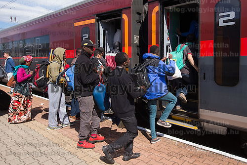 Illegal migrants traveling to Germany get on a train headed for Munich near Hegyeshalom (about 180 km West of capital city Budapest), Hungary on September 06, 2015. ATTILA VOLGYI