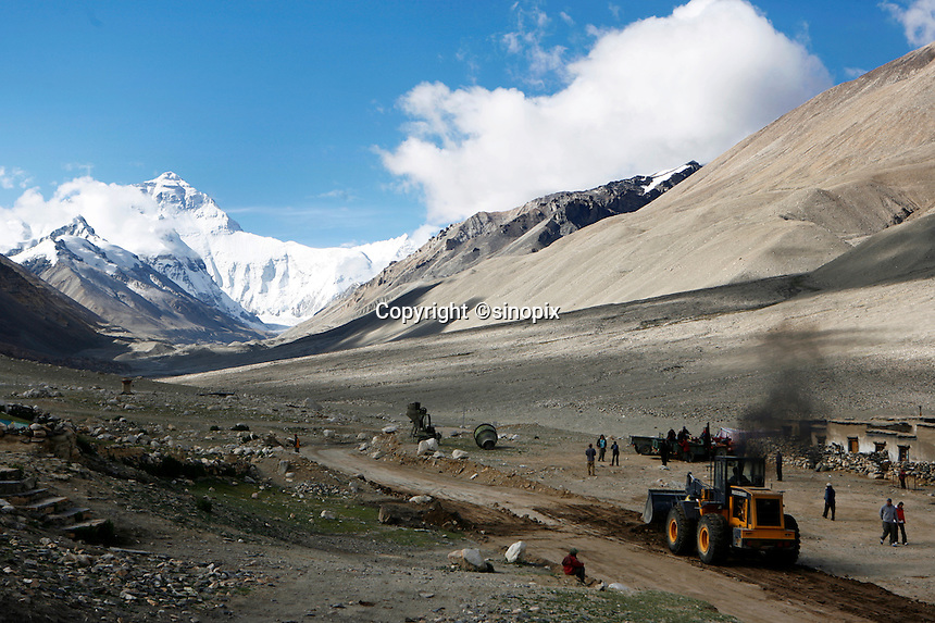 "A bulldozer belches smoke as it clears a road to everest base camp.<br /> China started building a controversial 67-mile ""paved highway fenced with undulating guardrails"" to Mount Qomolangma, known in the west as Mount Everest, to help facilitate next year's Olympic Games torch relay.<br /> Tibet, China<br /> July, 2007"