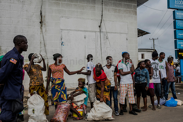 MONROVIA, LIBERIA - AUGUST 23, 2014:   Liberians carry/hold food as they are escorted by Liberian Police and Army personnel, to waiting friends and family, all residents of the West Point slum during the fourth day of the government's Ebola quarantine on their neighbourhood on August 23, 2014 in Monrovia, Liberia. The residents of Westpoint neighbourhood are forbidden from leaving the seaside slum, due to the Ebola outbreak in their community. More than 1,200 people have died due to the Ebola epidemic in West Africa.<br /> <br /> Daniel Berehulak for The New York Times