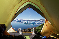 Camper's feet and view out door of tent onto icebergs on Sermilik Fjord near settlement of Tiniteqilaq, East Greenland