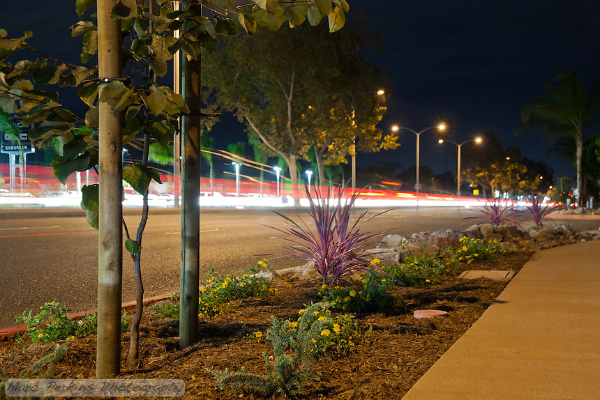 A long-exposure night image of the Harbor Blvd. class I bike path on Harbor between Fair and Merrimac in Costa Mesa, CA.  Many cars are seen driving on the street, though they're blurred into just red and white streaks.  Streetlights provide the only illumination.
