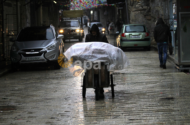 Palestinians walk under the rain, during a winter storm, in the West Bank city of Nablus, on December 18, 2016. Photo by Nedal Eshtayah