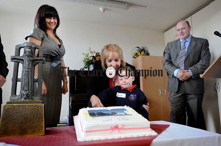 Mary Rockett, a junior infant of 50 years ago  and John Lynch, current junior infant, cut the cake at the 50th anniversary celebrations at Newmarket on Fergus National School, watched by principal Anne Mc Mahon and chairman of the board of management Michael Willis. Photograph by John Kelly.