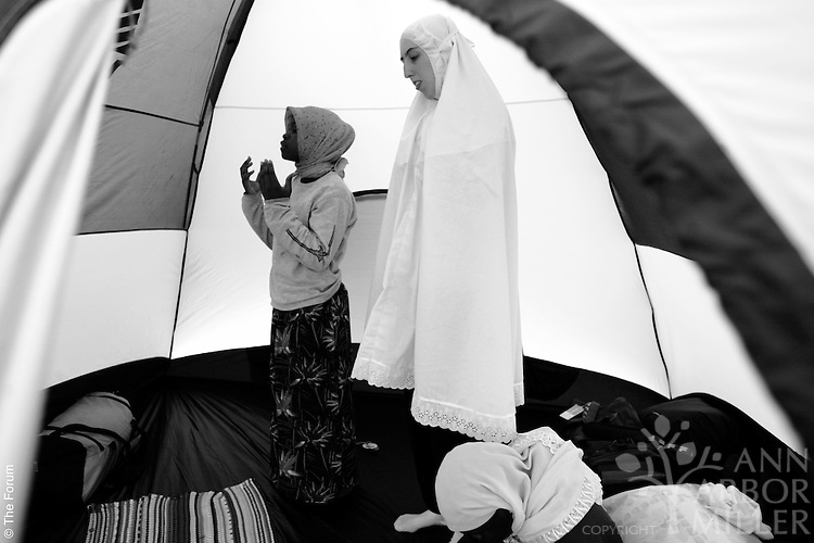 Fowzia Pitia (left) Jessica Nix (center) and Hawa Pitia (bottom right) briefly stepped away from post-lunch activities to pray inside one of two tents occupied by members of Girl Scout Troop 2005 during a weekend at Itasca State Park in northern Minnesota. Nix, 20, of Fargo assists adult leader Aisha Salih with the troop and its activities.