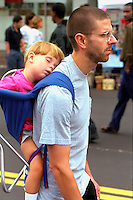 Dad carrying sleeping child in backpack at Cedarfest age 30 and 2.  Minneapolis Minnesota USA