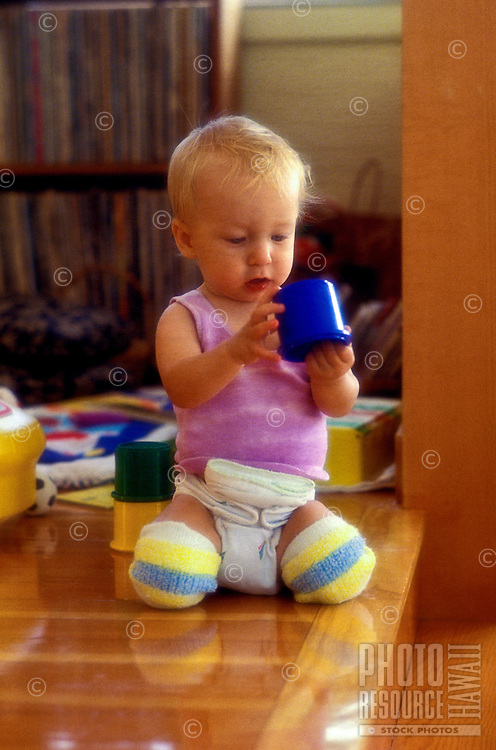 A cute blonde baby plays with some toys on the floor inside a home on Oahu.