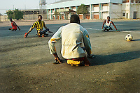Members of KPVTA practicing para-soccer. They can reach high speed by sitting on small wooden skateboards and pushing themselves by hands protected by flip-flops.