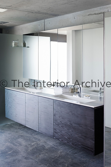 Granite flooring moves up the walls in the bathroom and reflects the soft grays of the indigenous landscape, as well as the facing cliffs.