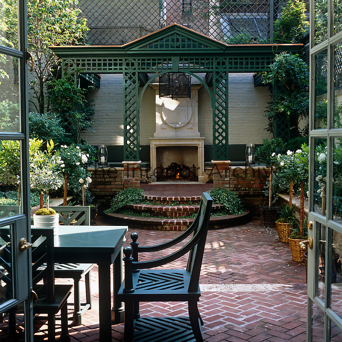 Seen through a pair of French windows the courtyard garden with an elegant garden room, complete with open log fire, situated under a trelissed awning at one end