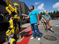 NWA Democrat-Gazette/JASON IVESTER<br /> William Ernesto of Rogers greets Transformers character Bumblebee Monday, June 12, 2017, outside the Wal-Mart Supercenter on Walnut Street in Rogers. The character is part of a five-month tour around Wal-Mart stores promoting the upcoming movie, Transformers: The Last Knight, which releases later this month. The tour will make stops at Wal-Mart stores in Fort Smith on Thursday and the Wal-Mart on Martin Luther King Jr Boulevard in Fayetteville on Thursday at 5:30.