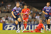 MELBOURNE, AUSTRALIA - JANUARY 23, 2010: Grant Brebner from Melbourne Victory runs with the ball as Fabian Barbiero from Adelaide United misses the ball in round 24 of the A-league match between Melbourne Victory and Adelaide United FC at Etihad Stadium on January 23, 2010 in Melbourne, Australia. Photo Sydney Low www.syd-low.com