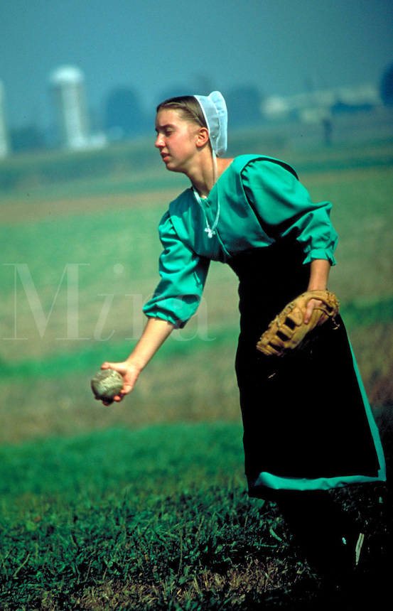 Amish teacher pitches softball during recess. Amish woman. Lancaster Pennsylvania United States Amish schoolyard.