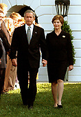 U.S. President George W. Bush looks somber as he and First Lady Laura Bush walk past members of the White House staff to observe the exact moment of the first terrorist attack on the World Trade Center at 8:46 AM two years ago at the White House in Washington, DC on September 11, 2003.<br /> Credit: Ron Sachs / CNP