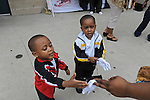 (L-r) Jarell Taylor, 2, and Javonte Taylor, 3, of Portage, Indiana receive white gloves as they enter U.S. Steel Yard Stadium before a hometown tribute to Michael Jackson begins in Gary, Indiana on July 10, 2009. Jackson died on June 25 at a Los Angeles hospital.
