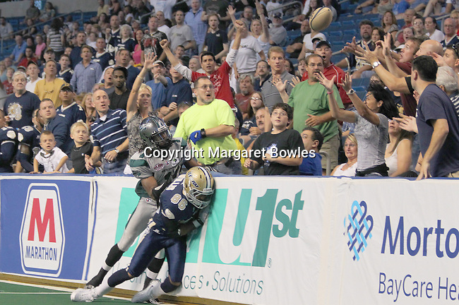 25 June 2010:  Battle Wing wide receiver Roland Cola and Storm defensive lineman Jermaine Smith struggle as the ball flies into the stands. The Tampa Bay Storm defeated the Bossier-Shreveport Battle Wings 78-39 at the St. Pete Forum in Tampa, Florida
