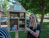 """NWA Democrat-Gazette/ANTHONY REYES @NWATONYR<br /> Michelle Wynn, with the 22nd class of Leadership Springdale, puts food in a """"Little Free Pantry"""" Monday, May 8, 2017 at the Springdale Housing Authority in Springdale. The pantry is the Leadership class' special project they designed, raised the money for and installed. The group installed five pantries around Springdale. One each at the Jones Center, Springdale Housing Authority, Springdale Police Department, Elmdale Baptist Church and the Iglecia Ministerio Pentecostal."""