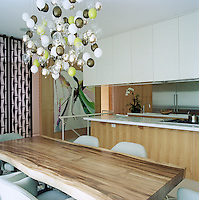 The dining room and kitchen area with a chandelier by Susan Etkins