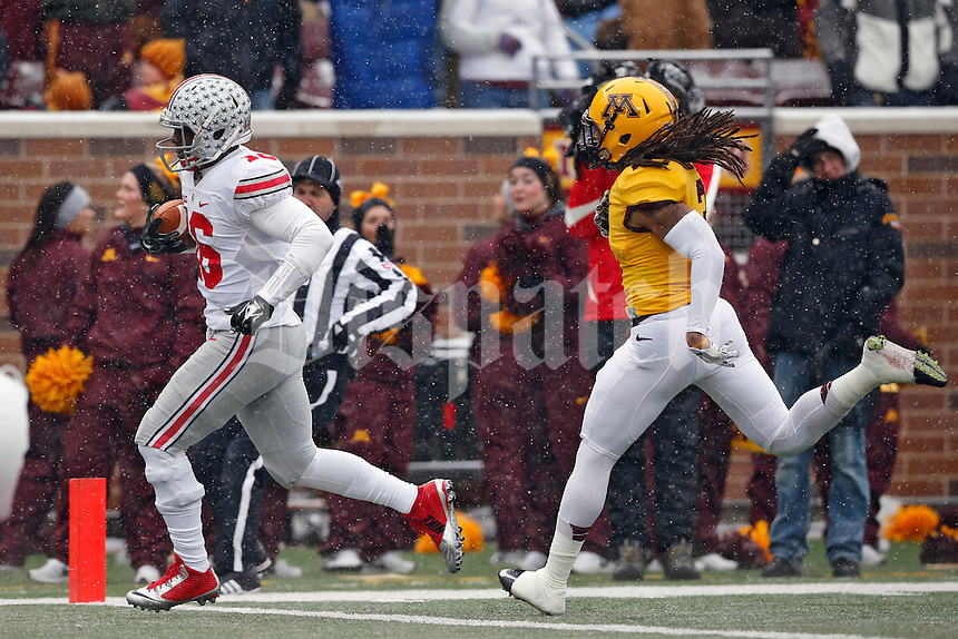 Ohio State Buckeyes quarterback J.T. Barrett (16) scores on a rushing touchdown after getting past Minnesota Golden Gophers defensive back Derrick Wells (3) during the 1st quarter at TCF Bank Stadium in Minneapolis, Minn. on November 15, 2014.  (Dispatch photo by Kyle Robertson)
