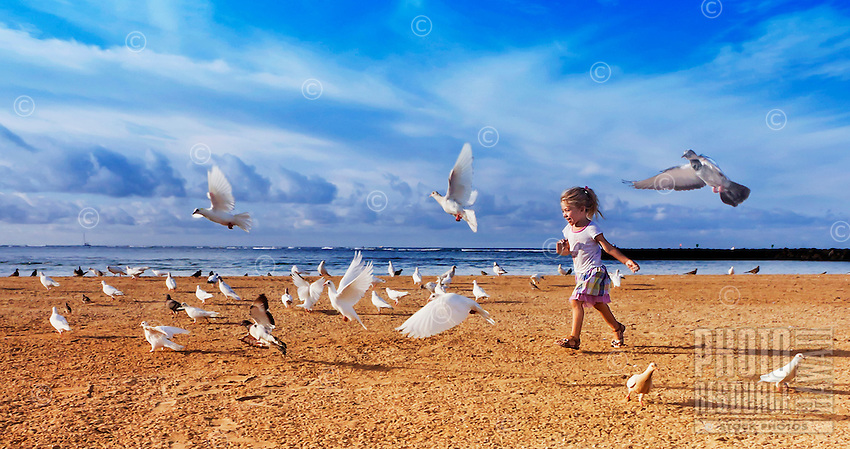 Child chasing birds on beach in Waikiki, Honolulu, Hawaii..