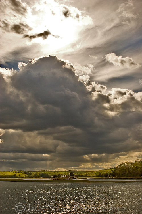 Thunderhead clouds in the sky over a river island house.