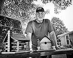 Black and white of man selling hand-made birdhouses. Farmersville OH