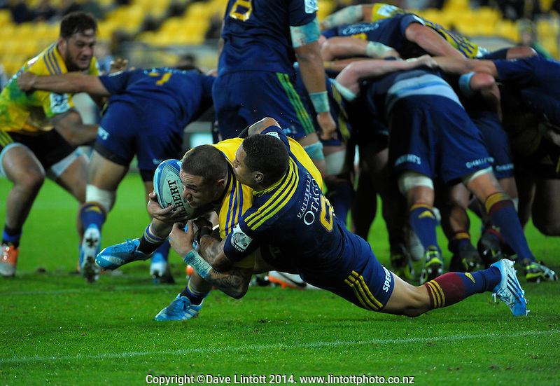 TJ perenara drives through the tackle of Aaron Smith to score during the Super Rugby match between the Hurricanes and Highlanders at Westpac Stadium, Wellington, New Zealand on Friday, 16 May 2014. Photo: Dave Lintott / lintottphoto.co.nz