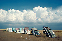 Cadillac Ranch environmental sculpture; cars halfway embedded vertically in the sand; a work of art constructed by The Ant Farm artists group, cumulus clouds in blue sky in background, art, artwork. RB0486037. Tp . Amarillo Texas, Cadillac Ranch.